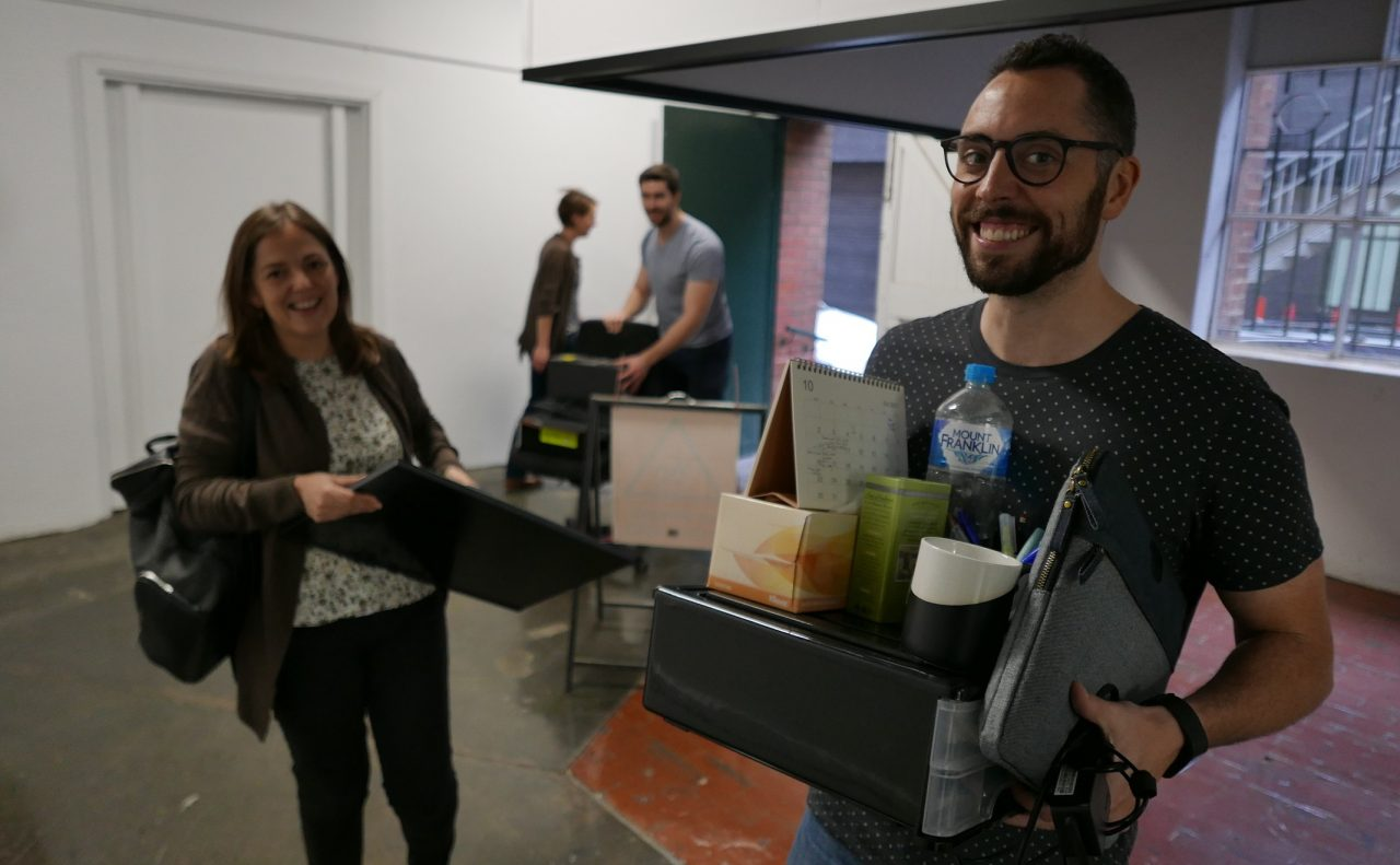 Justin, Liz and Alex carrying their belongings to the new office